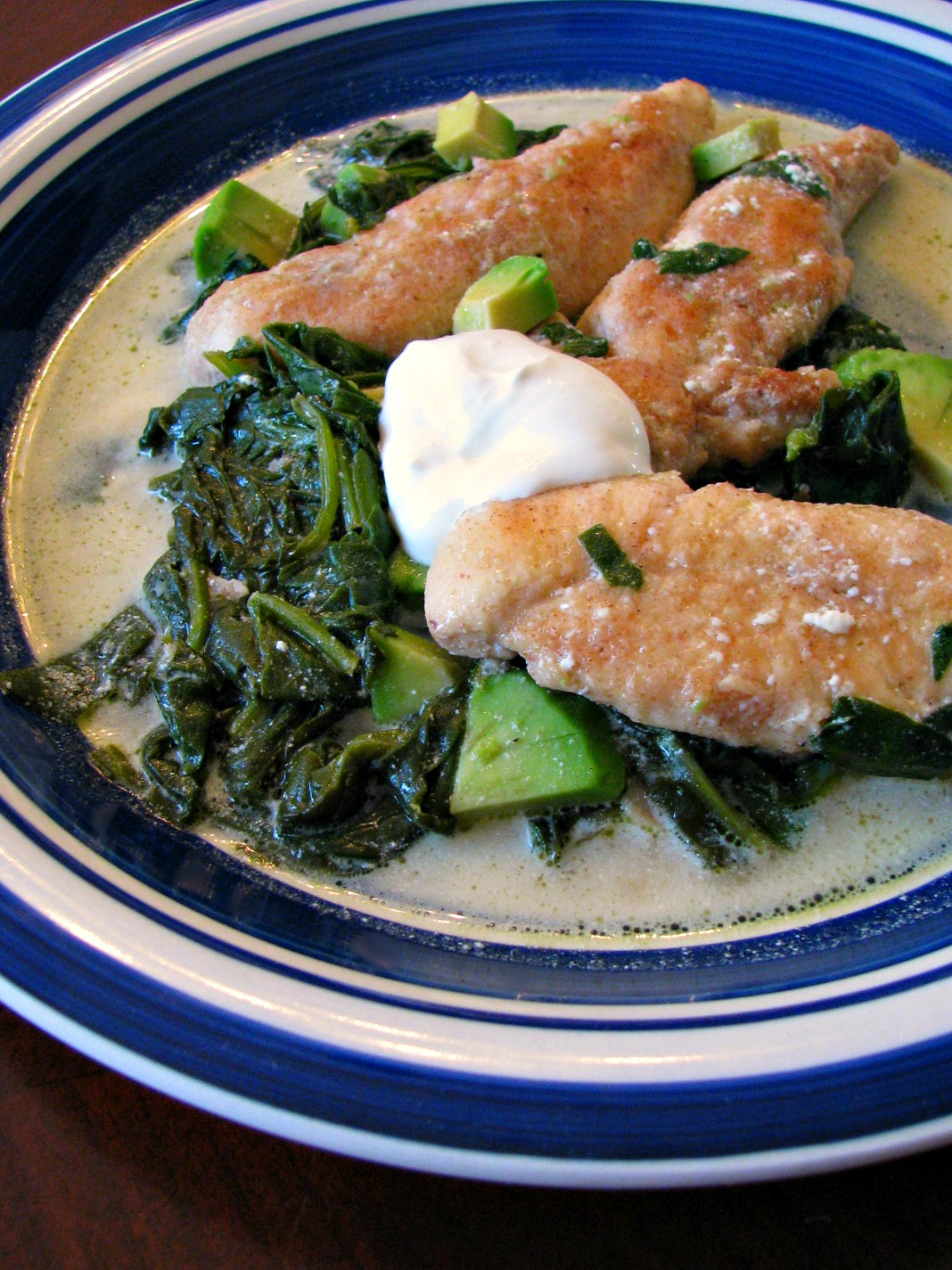 Skillet Chicken with Spinach and Avocado- Turn ordinary chicken tenders into a full meal your family will love with this Skillet Chicken with Spinach and Avocado! Tender chicken, sauteed spinach, diced avocado, simmered in chicken broth and finished with just a little bit of sour cream. Full of protein, iron, and healthy fats, this delicious dinner is ready in less than 30 minutes.