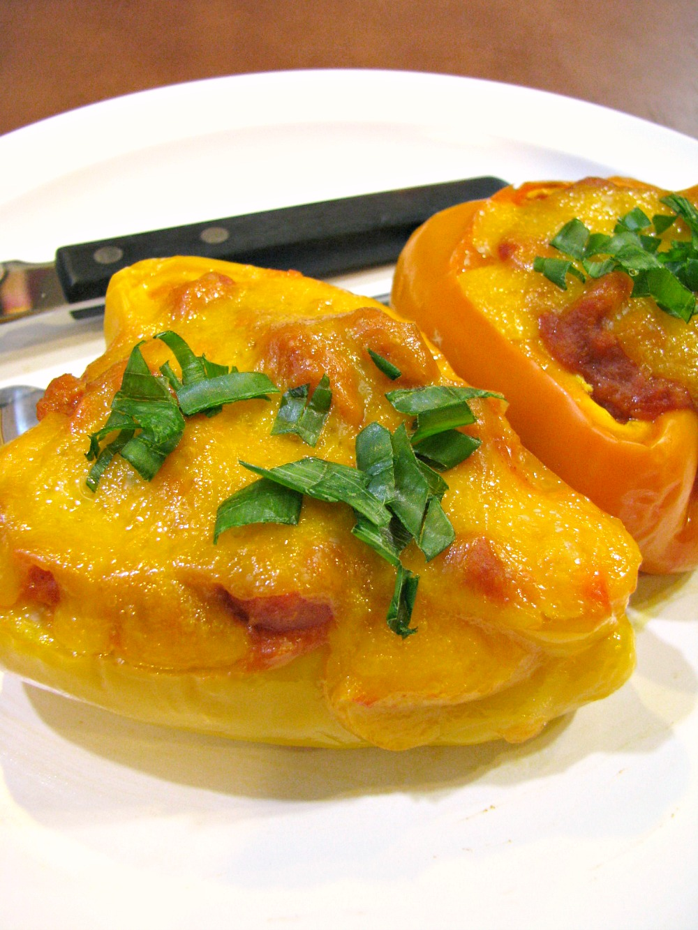 Cheesy, flavorful, and healthy Sloppy Joe Stuffed Peppers! These stuffed peppers are filled with ground chicken, traditional Sloppy Joe MANWICH sauce, pumpkin puree, carrots, celery, and Gouda cheese, then topped with cheddar cheese.