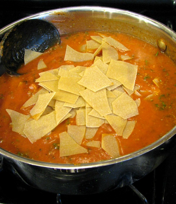 Uncooked lasagna noodles in sauce.